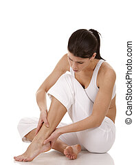 feet pain - brunette holding her feet on white isolated...