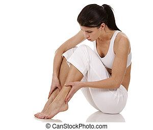 feet pain - brunette holding her feet on white isolated...