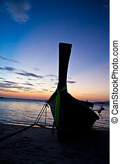 Silhouetted longtail boat thailand