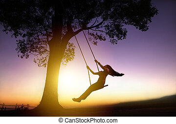 silhouette of happy young woman on a swing with sunset...