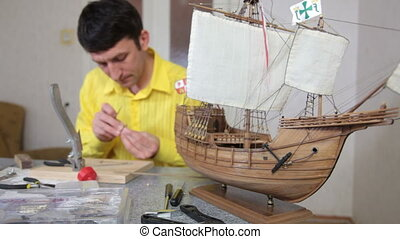 Model shipbuilding - Man making replica model of ship