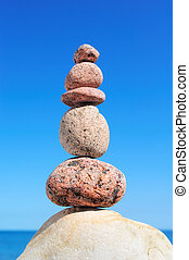 Steadfast - A stack of round pebbles on background the sky