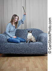happy young woman playing with cat
