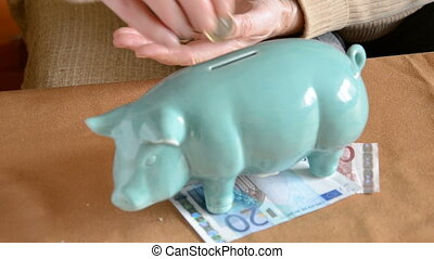 woman pensioner hands putting euro coins into piggy-bank