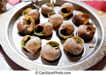 Escargots - Plate of escargot shells, with special tongs and...