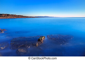 Submerged rocks, blue ocean, clear sky on bay beach sunset -...