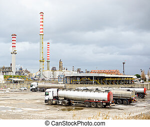 Oil refinery industry, smoke stacks and tanker lorry or...