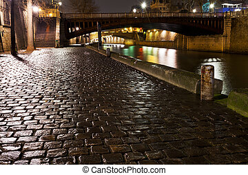 quay in Paris at night - cobblestone paved quay in Paris at...