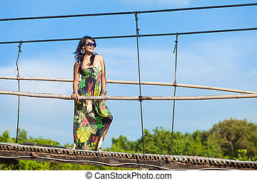 Young asian woman in floral dress suspension bridge in...