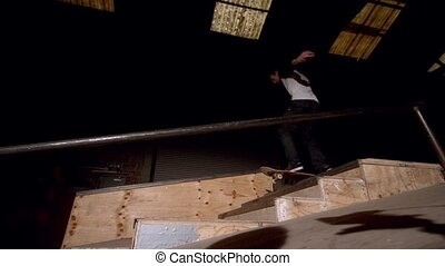 Skater doing large ollie down steps low angle view in slow...