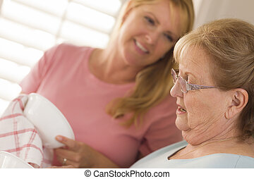 Senior Adult Woman and Young Daughter Talking in Kitchen