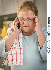 Shocked Senior Adult Woman on Cell Phone in Kitchen -...