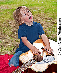 Young Boy Singing and Playing with Guitar - This young boy...