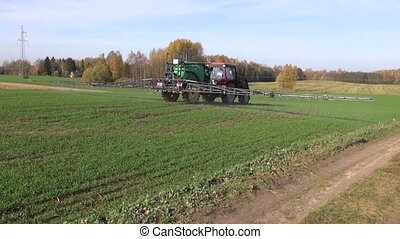 tractor spraying crop field