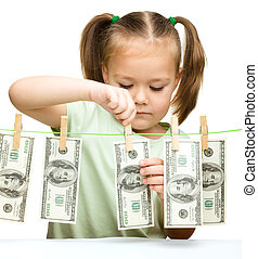 Cute little girl is playing with paper money