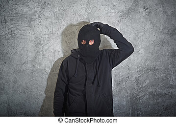 Confused burglar concept, thief with balaclava caught and...