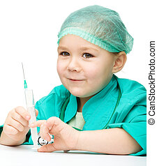 Cute little girl is playing doctor with syringe