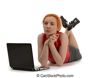 Thoughtful woman working on a laptop lying on her stomach on...