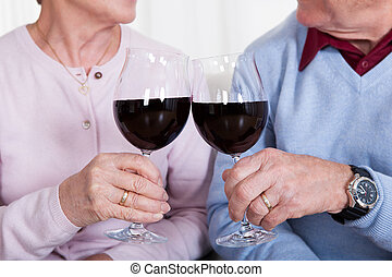 Senior Couple Toasting Glass Of Wine; Indoor
