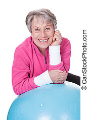 Senior Woman Leaning On Pilates Ball Over White Background