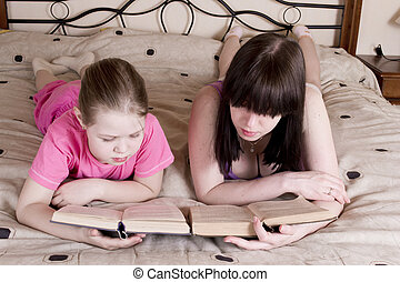 Girls reading  book on bed