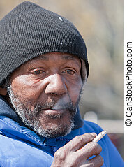 Homeless man smoking a cigarette outdoors during the day.