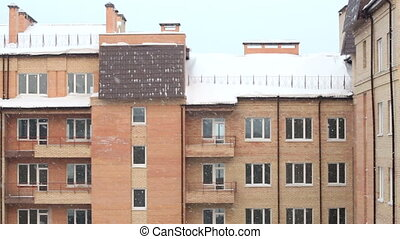 Snow against brick house.