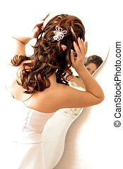 Bride adjusting hair in mirror - Rear view portrait of bride...