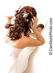 Bride adjusting hair in mirror