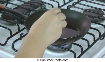 Egg being placed in a pan in the kitchen