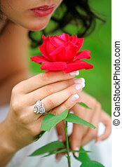 Woman holding single red rose