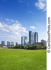 city park - City park under blue sky with Downtown Skyline...
