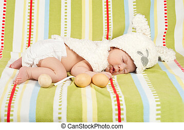 Easter newborn baby boy sleeping on blanket with fresh eggs...