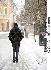 Man walking down the snowed city alley.