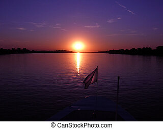 Purple sunset - purple sunset over dark river from boat