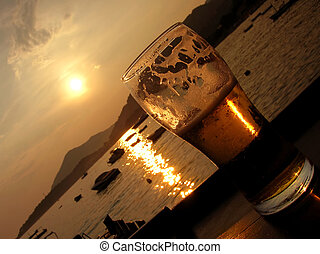 Beer sunset - beer glass over sea sunset highlighted...