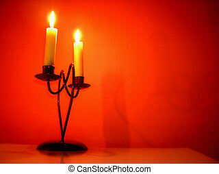 Candles over orange - two burning candles on candlestick...