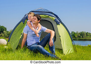 Family camping - Father with his daughter resting on the...