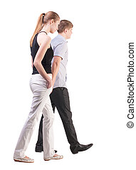 Back view of walking young couple (man and woman). Rear view...