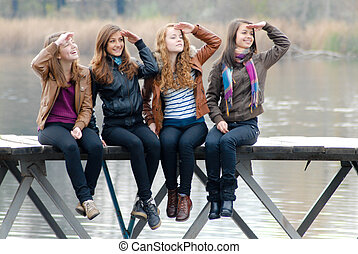 Four school girls sitting on river bridge - Four happy...