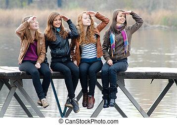 Four school girls sitting on river bridge - Four happy...