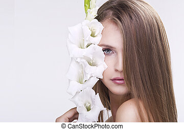 Beauty face of the young beautiful woman with flower. Female...