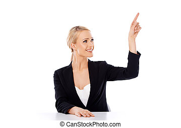 Blond business woman sitting at the desk and pointing...