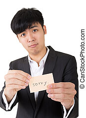 sorry word - Asian businessman holding a card written on...