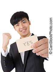 yes sign - Asian businessman holding a card written on yes,...