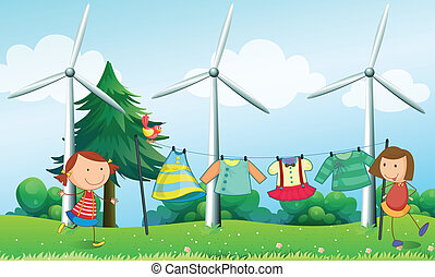 Two girls hanging their clothes near the windmills -...