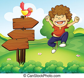 A happy young boy beside the three wooden arrows