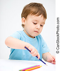 Little boy is drawing on white paper