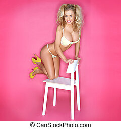 Sexy Blonde Woman In Bikini Kneeling On Chair Against Pink...