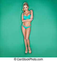 Serious Blonde Young Woman In Bikini On Turquoise Background
